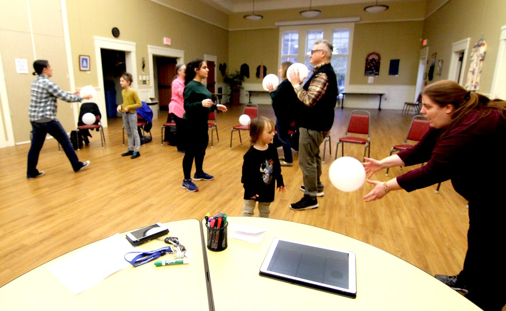 . A group playing an inactive game as they are in a class of Swahili for beginners as part of Read Across Africa program at the Townsend Public Library, led by teacher Markus Lewis (in back holding a white balloon).  Nashoba Valley Voice/ David H. Brow