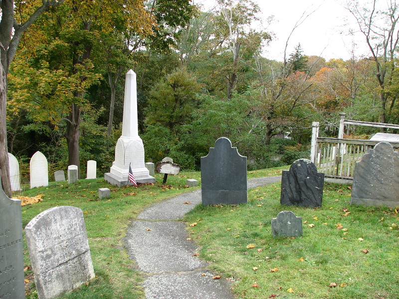 Approaching the monument (the white obelisk). To locate the monument, enter the cemetery via the main entrance on School Street at Town Square. Climb the stairs and brick walkway to the top of the hill. Turn left on the paved path, then take an immediate right on another paved path. Follow that along the crest of the hill nearly to its end, and look for the distinctive monument on your left.