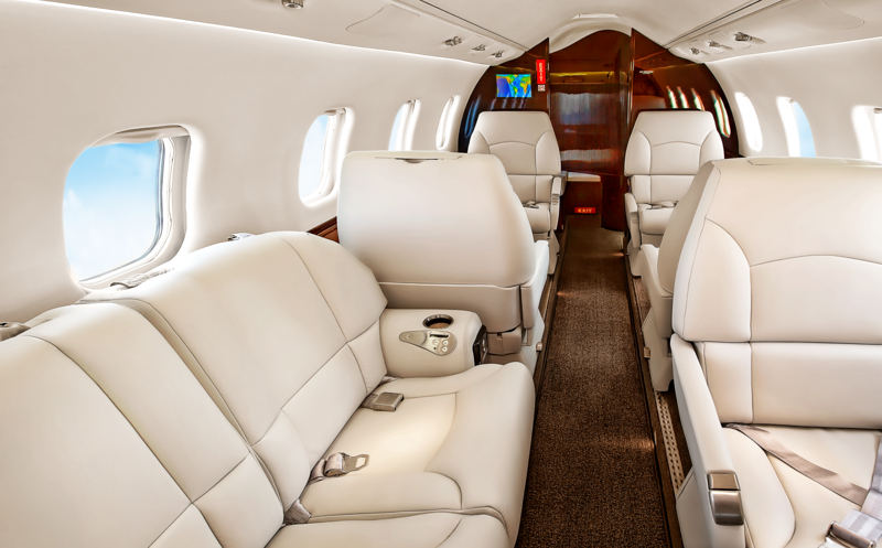 This well-lit, slightly-angled aircraft interior photo puts spacious seating on display while highlighting the various collaborative potential of this passenger aircraft.