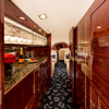 This single photo puts the spacious, well-appointed interior on display in lighting that presents the details in the wood trim while also managing to showcase the deep passenger cabin, wide walkways and a touch of concierge services.