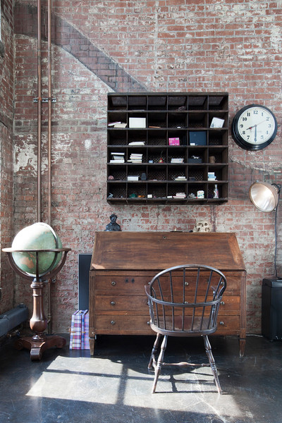 A view of the office with with originally exposed brick walls of this once Power Station.  This antique desk folds down to expanded and is paired with a vintage industrial orgainzation once used in a factory now is used to organize modern office supplies as seen on HGTV's Million Dollar Rooms.