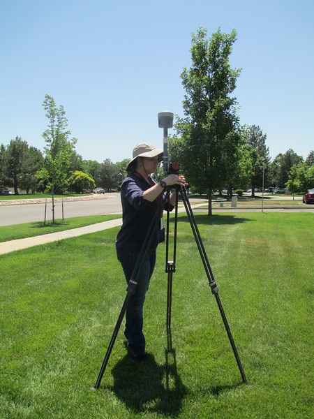 Laura Fakarhai performs leveling procedures on a GPS station.