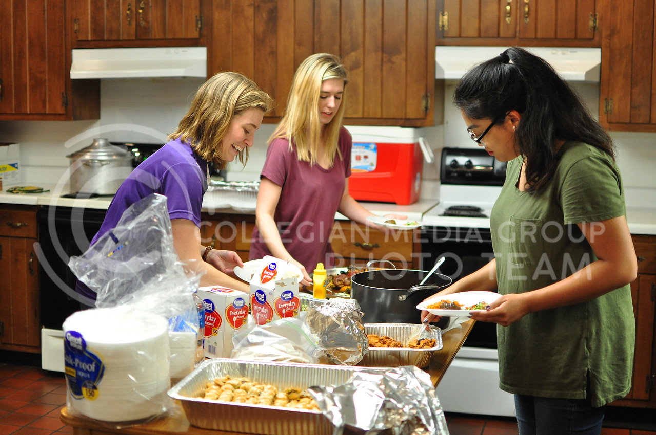 From left Amy Hall, International Student and Scholar Services, Kiara O'Dea Junior in Secondary Education and French, and Savannah Rattanavong Senior in Journalism and Mass Communications, prepare food for Internation Coffee Hour in Manhattan, Kan. Spetember 22, 2017 (Blake Reid | Collegian Media Group)