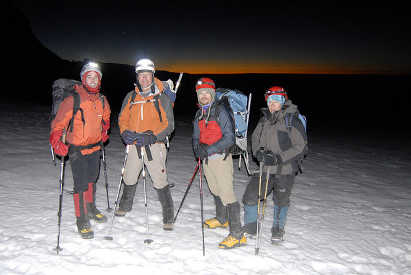 The team high on Iztaccihuatl pauses for a photo as the sun begins to reveal the first signs of morning in the distance.