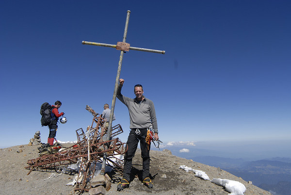 Kurt Wedberg poses next to one of several crosses on the summit