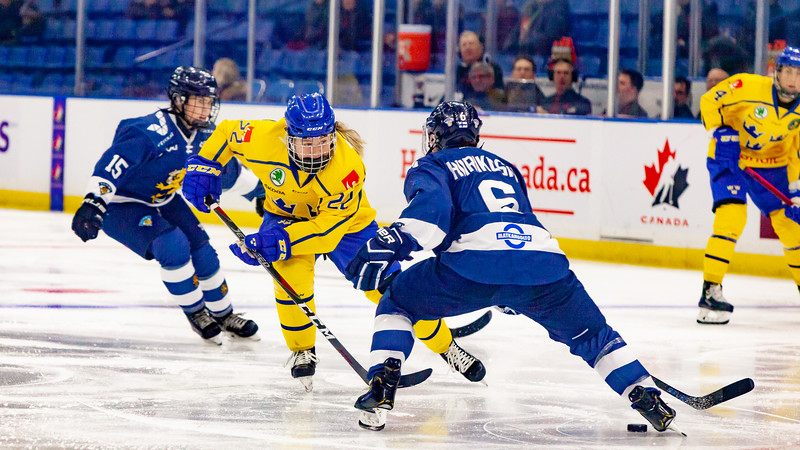 November 10, 2018 - Saskatoon, SK - Team Sweden forward Lina Ljungblom plays the puck past Finnish defender Jenni Hiirikoski during Bronze medal game play.