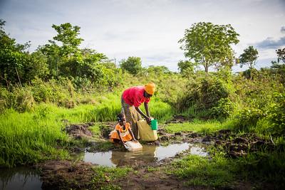 UG579, Acet, Uganda, WASH, Jamia Babirye, mother, and Aumal Sekiranda, child, fetch water behind their hut