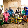 Compassion child Adjara Roukietou (colorful dress) and family, including siblings: Sita (youngest) Isa (green shirt), Souleymane (pink shirt), Aminata (mom 1), and Zalissa (mom 2), and Inousa Zalle (father).