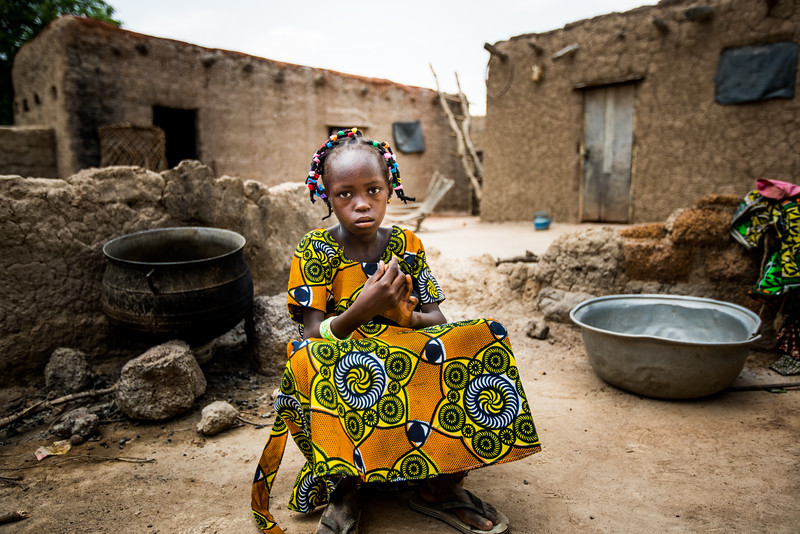 Compassion child Adjara Roukietou (colorful dress) and family, including siblings: Sita (youngest) Isa (green shirt), Souleymane (pink shirt), Aminata (mom 1), and Zalissa (mom 2), and Inousa Zalle (father).