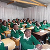 Students sit attentively in a classroom.  the uniforms are also provided by the school.