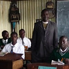 Principal of the school, Dionisio Kiambi with students in a classroom.