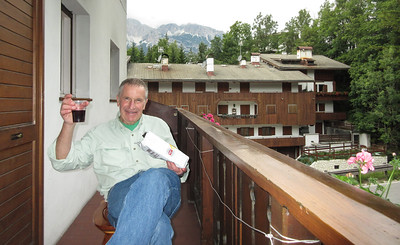 Roger is enjoying a glass of wine and some snacks on the balcony of our room.