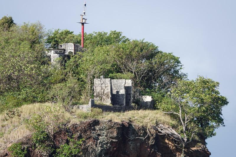 Old concrete buildings on a harbor entrance rock bluff, Castries, Saint Lucia.