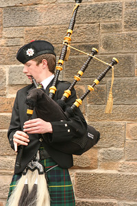 A kid playing the bagpipes on the Royal Mile