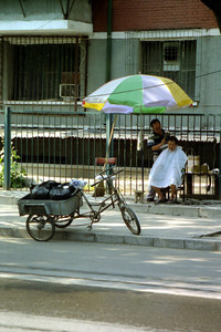 A Chinese man giving a haircut on the sidewalk.  Pedro and I saw this as we biked through Beijing. ... August 4, 2004 ... Copyright Robert Page III