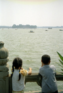 Two children looking out at Kumming Lake, a man made lake, in the Summer Palace complex. ... August 5, 2004 ... Copyright Robert Page III