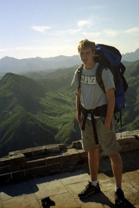 Rob Page on the Great Wall of China with it stretching out on the mountains behind him. ... August 3 2004 ... Copyright Robert Page III