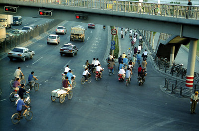 An intersection in the downtown area of Shanghai.  Notice that the traffic lights have special lights for the bikes because there are so many. ... August 6, 2004 ... Copyright Robert Page III