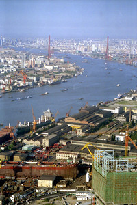 The industrial side of Shanghai with a boatyard in the foreground.  Then there are some factories/warehaouse where ships are unloading and in the background you can see the Yangpu Bridge gracing the Huangpu River. ... August 9, 2004 ... Copyright Robert Page III