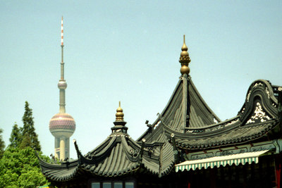 The Pearl TV Tower rising above one of the temples in the Yu Yuan Gardens in Shanghai Old City. ... August 9, 2004 ... Copyright Robert Page III