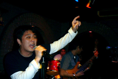 "The vocalist from the live band at ""Dusk Til Dawn"" in Wan Chai, Hong Kong.  This was a very good live band who could play a variety of covers. ... July 30, 2004 ... Copyright Robert Page III"