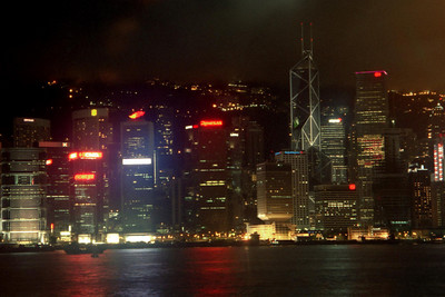 The Hong Kong skyline at night from Tsim Sha Tsui in Kowloon.  Notice the three on the building to the right.  This would race up the building from time to time and then the building would erupt into lights and color.  The tall building in the middle is the  Bank of China Tower (367m/1,205f, 72 stories, built in 1990). ... July 28, 2004 ... Copyright Robert Page III