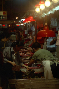 Watching workers in stalls scale live fish and gut chickens at the Peiho Mark in Sham Shui Po. ... July 30, 2004 ... Copyright Robert Page III