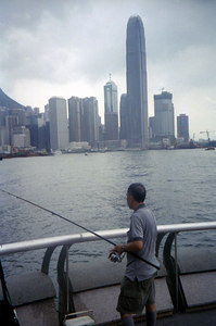 A fisherman with all his gear at the International Convention Center with the Two International Finance Center rising above him. ... July 28, 2004 ... Copyright Robert Page III