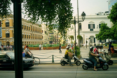 Leal Senado Square.  This is the main square in downtown Macau.  It is designed with a wave-patterned mosaic by the Pourtugese.   In front you will see all the mopeds that were characteristic of the city. ... July 27, 2004 ... Copyright Robert Page III
