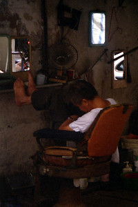 A barber hard at work at his shop in a back alley of Macau. ... July 27, 2004 ... Copyright Robert Page III