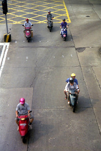The mopeds of Macau.  They would weave through traffic at lights and be the first ones through intersections when the light turned green.  Notice that they are all wearing helmets too. ... July 27, 2004 ... Copyright Robert Page III