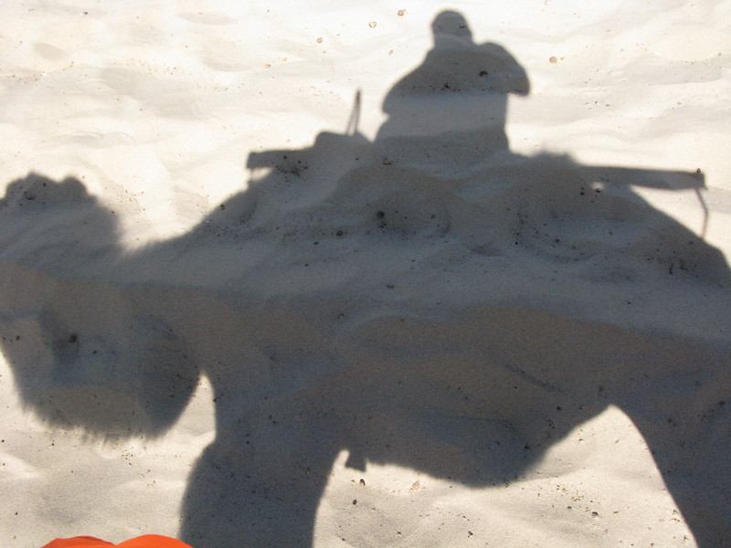 Tourist and his shadow on the Singing Sand Dunes