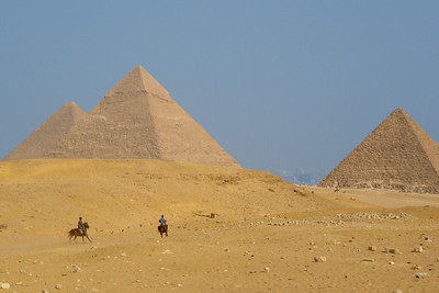 The Giza pyramids with horseman enjoying the day.  You can see modern Cairo in the background between the pyramids - Giza, Egypt ... November 20, 2006 ... Photo by Rob Page III