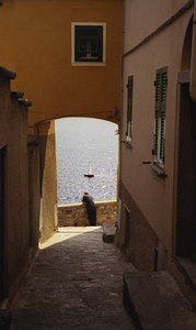 A man looks wistfully out at the sea as a sailboat passes by - Manarola, Cinque Terre, Italy. ... July 9, 2001 ... Photo by Rob Page III