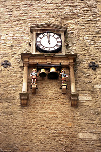 The clock of Carfax tower in Oxford, England.  The little boys hanging below are called quarter boys because they hit the bells on the quarter hours. ... June 20, 2001 ... Photo by Rob Page III