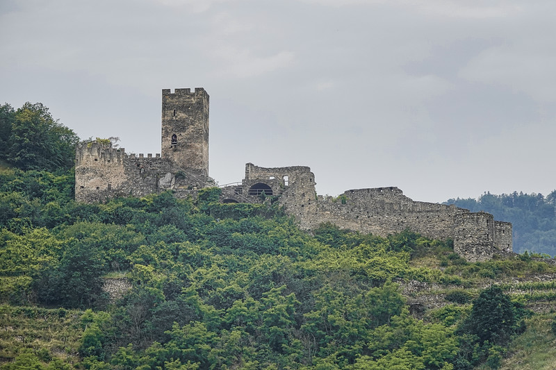 The ruins of 13th-century Medieval Hinterhaus Castle above Spitz in Lower Austria.  The ruins of the Hinterhaus Castle originate from the 12th century. The castle dates back to the time of Kuenringers rule when it served as a strategic stronghold. From here they were able to rule the entire Wachau valley. Touring the ruins with the famous Red Gate gives you a good impression of what medieval defence methods were like.
