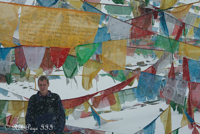 Rob with prayer flags at a pass on the way from Tingri to Nepal - Tibet, China ... May 27, 2014 ... Photo by Emily Page