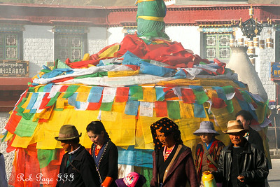Pilgrims walking the Barkhor Kora in front of prayer flags - Lhasa, Tibet, China ... May 21, 2014 ... Photo by Rob Page III