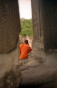 An Apsaras gaurds over the priest as he looks out at the jungle of Cambodia from Angkor Wat. ... August 14, 2004 ... Copyright Robert Page III