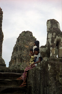 Little Cambodian children playing on the temples.  These one kept coming up to me with American coins and asked for bills or riel. ... August 15, 2004 ... COpyright Robert Page III