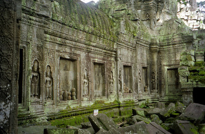 Ta Prohm.  Notice the Asparas along the wall.  Archeaologists have left this temple as it was when the European explorers discovered Angkor Wat.  The trees grow through and out of the ruins. ... August 15, 2004 ... Copyright Robert Page III
