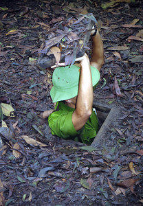 Our guide lowering himself into a Vietcong tunnel in Cu Chi.  Cu Chi was a pocket of resistance northwest of Saigon. ... August 12, 2004 ... Copyright Robert Page III
