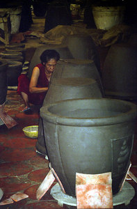 An old lady molding clay pots that are sold at American gardening centers. There is a lot of clay in the area of the Mekong Delta.  The clay also allowed  the Vietcong to construct their tunnels. ... August 13, 2004 ... Copyright Robert Page III