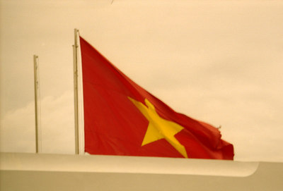 The Vietnamese flag waves in the air above the Reunification Palace. ... August 11, 2004 ... Copyright Robert Page III