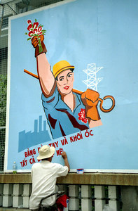 A Vietnamese painting a new billboard for the country. ... August 11, 2004 ... Copyright Robert Page III