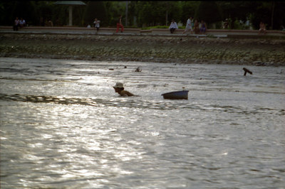 A man swimming in the river.  After seeing all the garbage I don't know how anyone could swim in this river. ... Copyright Robert Page III