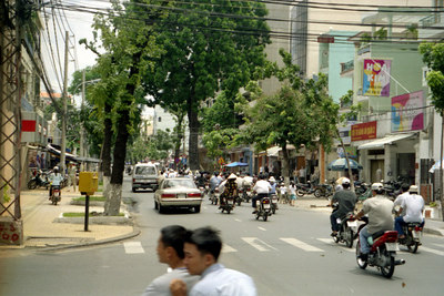 One of the busy streets in Saigon.  Notice all of the mopeds.  I think they outnumberred cars 3-1. ... August 11, 2004 ... Copyright Robert Page III