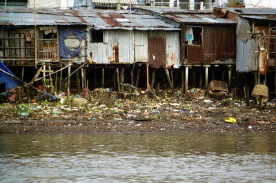 Shanties on poles hoping that the river never rises above its banks.   Notice all of the garbage. ... August 11, 2004 ... Copyright Robert Page III