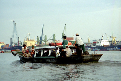 A group of men being shuttled across the river after work. ... August 11, 2004 ... Copyright Robert Page III