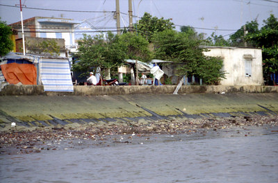 Some poor people living along the far bank of the Mekong.  Notice all the trash along the bank.  I saw people literally walk to the edge of the river and throw trash into the water. ... August 11, 2004 ... Copyright Robert Page III